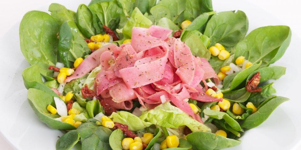 Salade met spinazie, mais, rode ui en zongedroogde tomaten, rammenas en rode bietensap